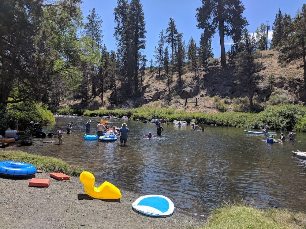Families playing in the river along the picnic area